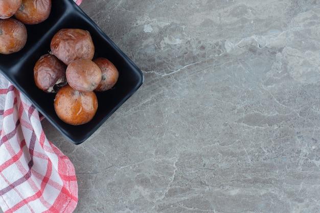 Bovenaanzicht van vers rijp biologisch mispelfruit in zwarte kom over grijs oppervlak