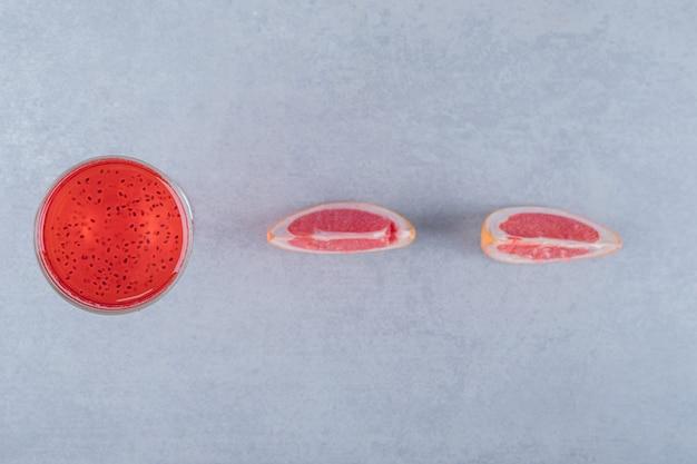 Bovenaanzicht van vers sap met plakjes grapefruit op grijze ondergrond