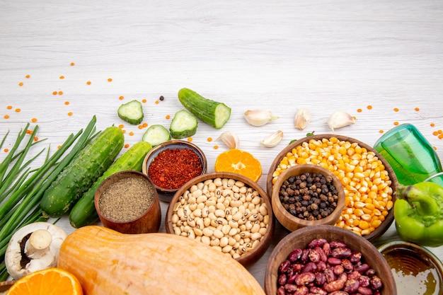 Bovenaanzicht van vers voedsel en kruiden groenten op de bodem op witte tafel