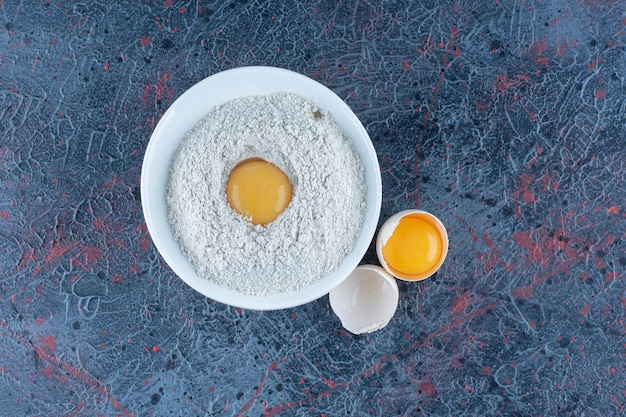 Bovenaanzicht van vers wit kippenei gebroken met dooier en eiwit.