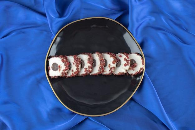 Bovenaanzicht van vers zelfgemaakt gesneden koekje op zwarte plaat over blauwe tafel.