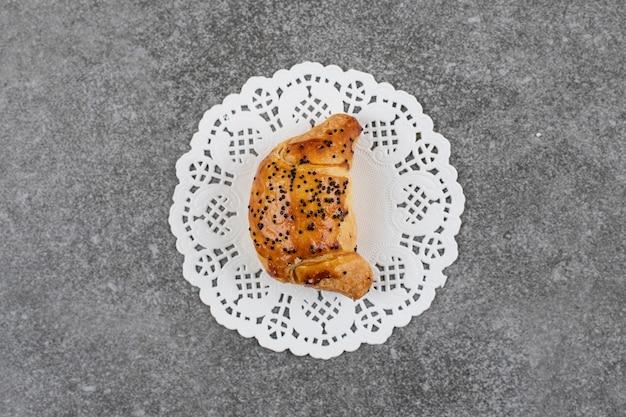 Bovenaanzicht van vers zelfgemaakt koekje op wit servet over grijs oppervlak