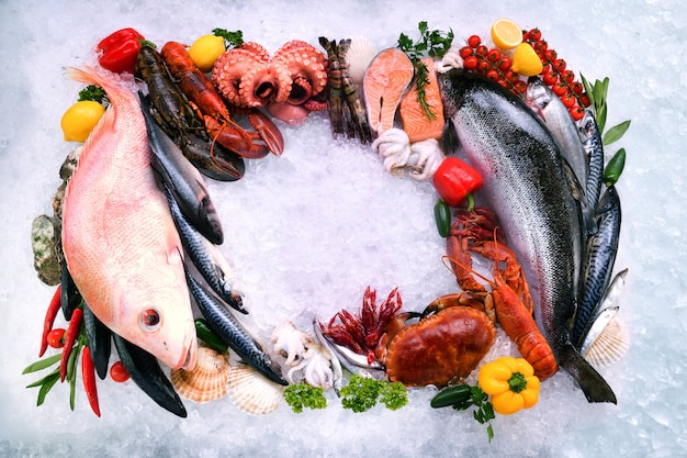 Bovenaanzicht van verscheidenheid aan verse vis en zeevruchten met copyspace op ijs