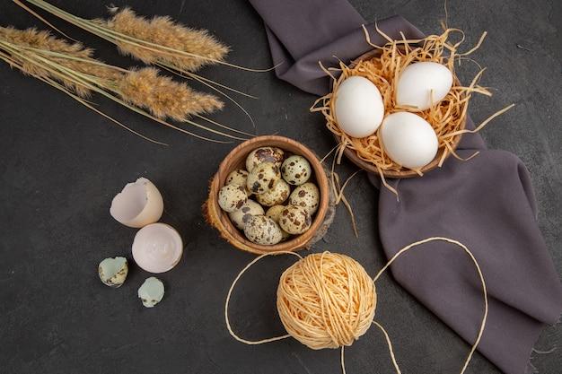 Bovenaanzicht van verschillende biologische eieren in een bruine pot touw spike zwarte handdoek op donkere achtergrond