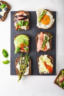Bovenaanzicht van verschillende bruschettas, sandwiches met verschillende gezonde fillihgs geserveerd op een donkere plaat