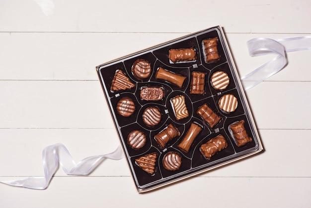 Bovenaanzicht van verschillende chocolade pralines in vak op witte houten achtergrond.