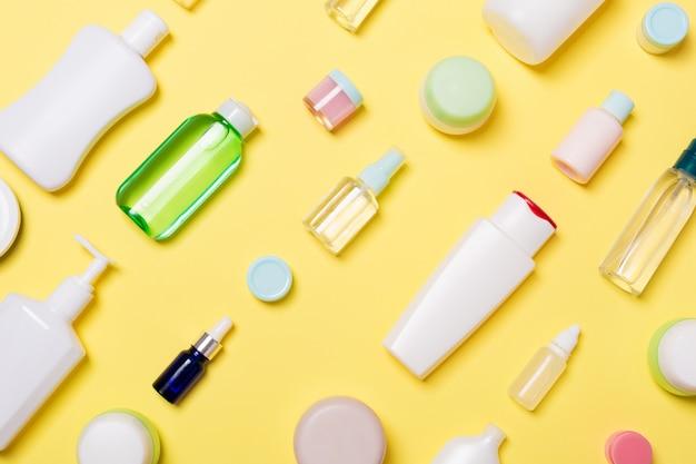 Bovenaanzicht van verschillende cosmetische flessen en container voor cosmetica op geel. plat lag samenstelling met copyspace