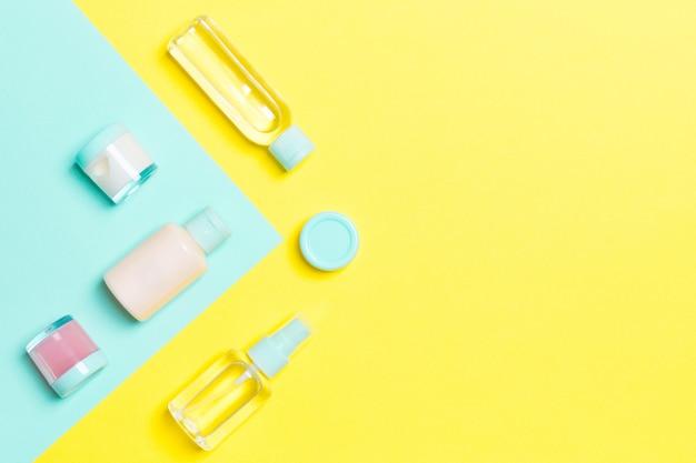 Bovenaanzicht van verschillende cosmetische flessen en container voor cosmetica op gele en blauwe achtergrond. plat lag samenstelling met kopie ruimte