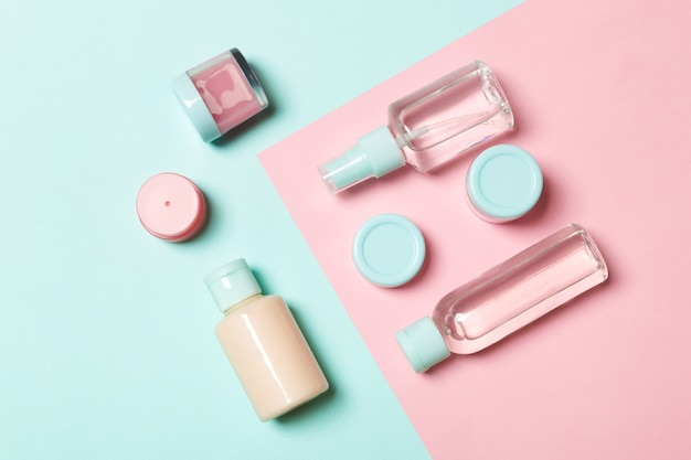 Bovenaanzicht van verschillende cosmetische flessen en container voor cosmetica op roze en blauw. plat lag samenstelling met copyspace