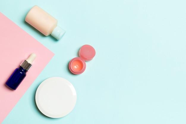 Bovenaanzicht van verschillende cosmetische flessen en container voor cosmetica op roze en blauwe achtergrond. platliggende compositie met kopieerruimte.