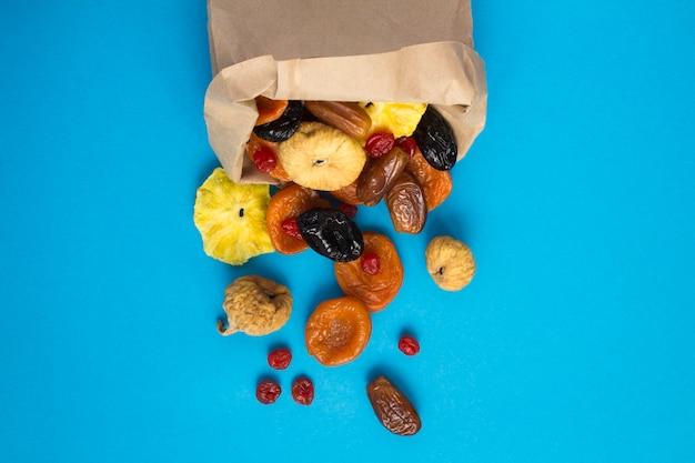 Bovenaanzicht van verschillende gedroogde vruchten in een papieren zak op de blauwe achtergrond