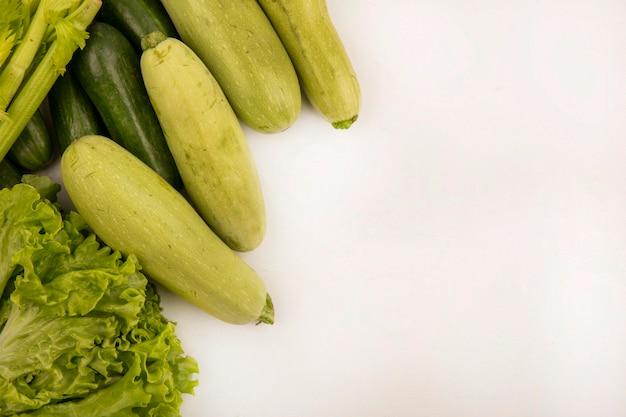 Bovenaanzicht van verschillende groenten zoals sla, selderij, komkommers en courgettes geïsoleerd op een witte muur met kopie ruimte