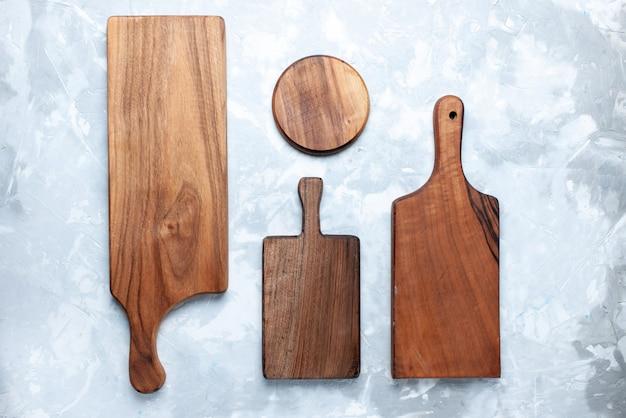 Bovenaanzicht van verschillende houten bureau, s voor voedsel geïsoleerd op licht, houten houten bureau,