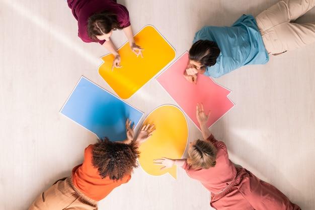 Bovenaanzicht van verschillende jonge vrouwen en man die met papieren tekstballonnen op de vloer liggen en bespreken wat ze erop moeten schrijven