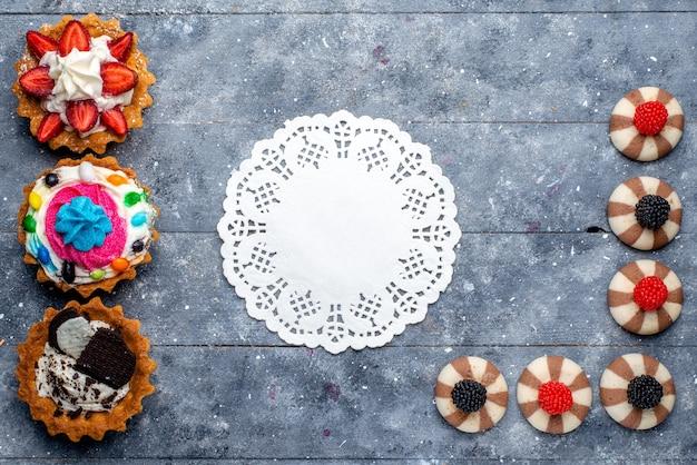 Bovenaanzicht van verschillende kleine cakes met gesneden fruit, snoepjes, chocolade en bessen op grijs bureau, koekjeskoekje zoete suiker bakken