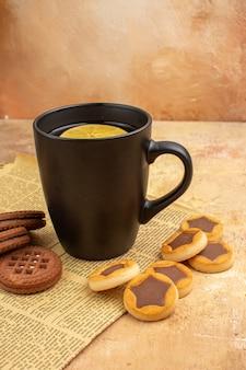 Bovenaanzicht van verschillende koekjes en thee in een zwarte kop op gemengde kleur achtergrond