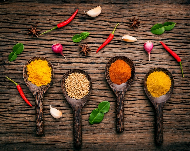 Bovenaanzicht van verschillende kruiden en specerijen in lepel op rustieke houten bruin