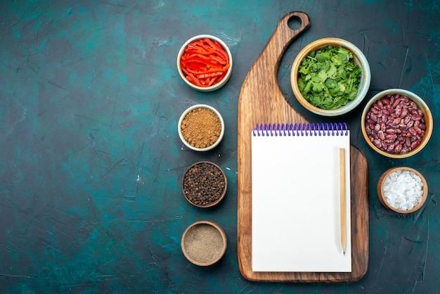 Bovenaanzicht van verschillende kruiden met greens en bonen kladblok op donker bureau, zout groen kruiden