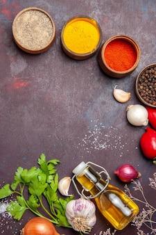 Bovenaanzicht van verschillende kruiden met groenten op donkere tafel
