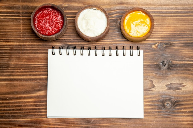 Bovenaanzicht van verschillende kruiden met notitieblok op bruin houten tafel pittige peper kleur beurt