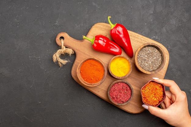 Bovenaanzicht van verschillende kruiden met rode peper op zwart