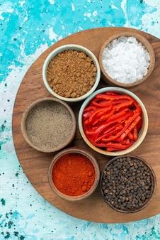 Bovenaanzicht van verschillende kruiden paprika gesneden rode kille peper op lichtblauw, peper zout product