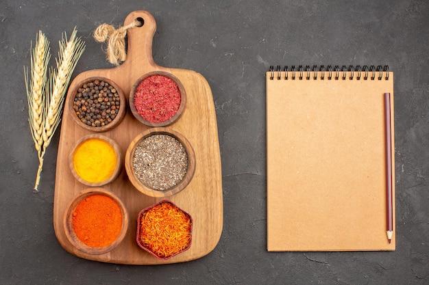 Bovenaanzicht van verschillende kruiden pittige ingrediënten in potten met notitieblok op zwart