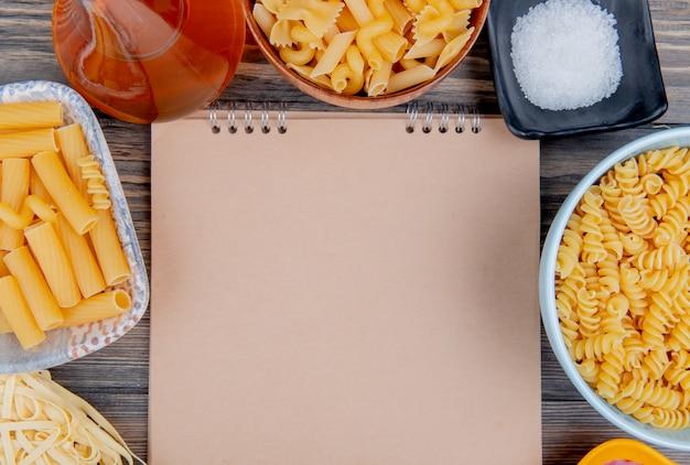 Bovenaanzicht van verschillende macaronis als ziti rotini tagliatelle en anderen met gesmolten boterzout rond notitieblok op hout met kopie ruimte