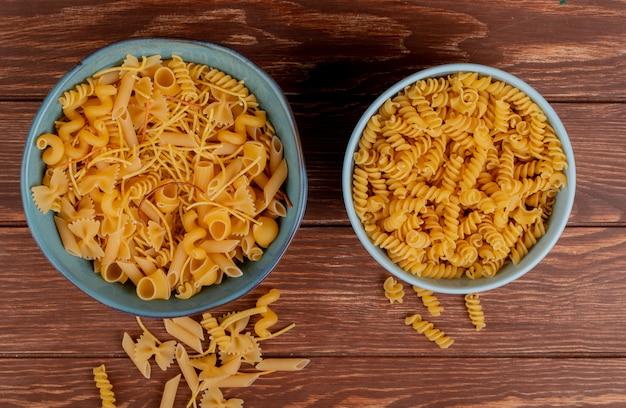 Bovenaanzicht van verschillende macaronis en rotini macaronis in kommen en op hout