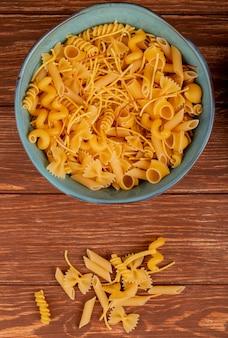 Bovenaanzicht van verschillende macaronis in kom en op hout