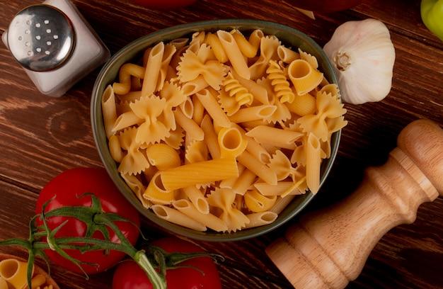 Bovenaanzicht van verschillende macaronis in kom met zout tomatenknoflook op hout