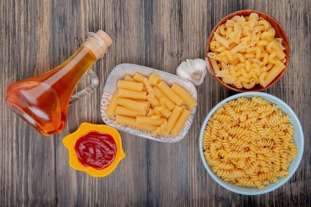 Bovenaanzicht van verschillende macaronis zoals ziti rotini en anderen met knoflook gesmolten boter en ketchup op hout