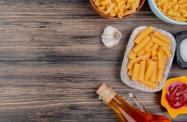 Bovenaanzicht van verschillende macaronis zoals ziti rotini en anderen met knoflook gesmolten boterzout en ketchup op hout met kopie ruimte