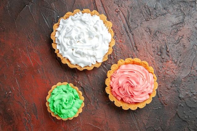 Bovenaanzicht van verschillende maten kleine taartjes met groene, roze en witte banketbakkersroom op donkerrood oppervlak