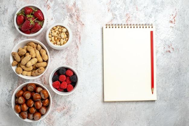 Bovenaanzicht van verschillende noten, hazelnoten, pinda's en confitures op witte ondergrond