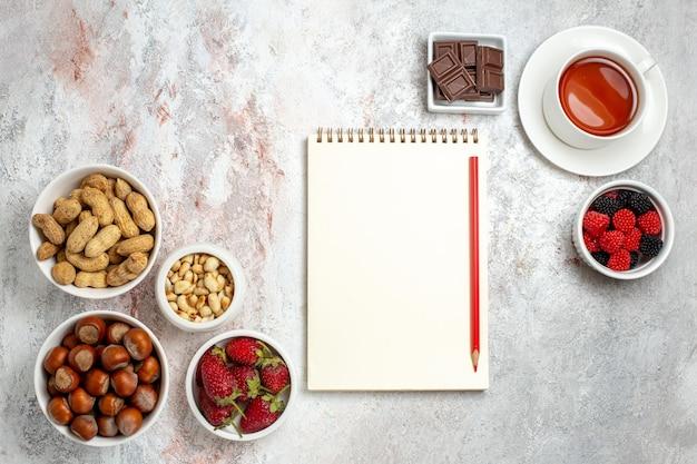 Bovenaanzicht van verschillende noten, hazelnoten, pinda's en kopje thee op witte ondergrond