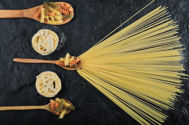 Bovenaanzicht van verschillende ongekookte pasta op donker.