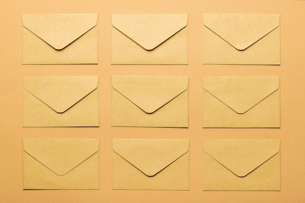 Bovenaanzicht van verschillende papieren enveloppen op een papieren achtergrond. plat leggen.