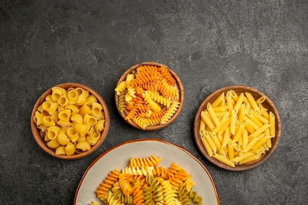 Bovenaanzicht van verschillende pasta samenstelling rauw product binnen platen op grijs