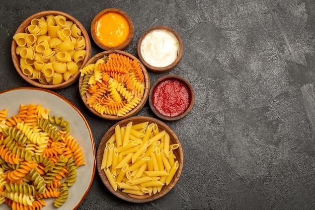 Bovenaanzicht van verschillende pasta samenstelling rauw product binnen platen op zwart