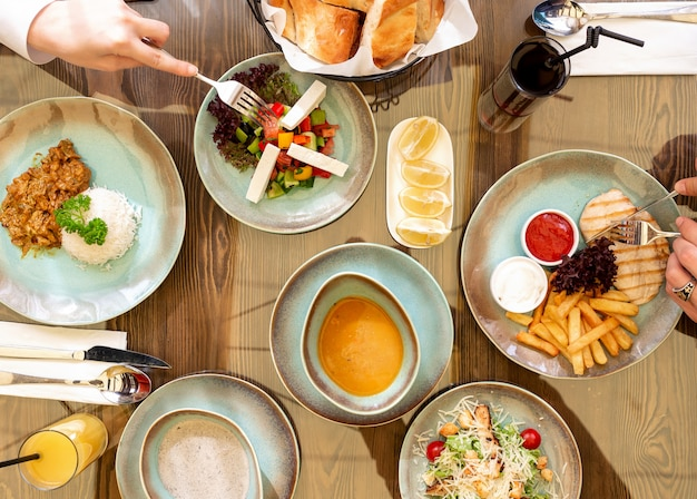 Bovenaanzicht van verschillende platen van voedsel fo diner groente salade met fetacheese rijst gegrilde kip met frietjes