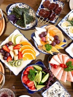 Bovenaanzicht van verschillende platen van voedsel voor breakfst fruitsalades gebakken eggr met kruiden ham