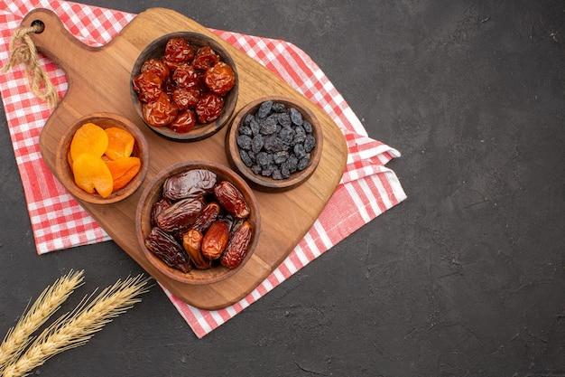 Bovenaanzicht van verschillende rozijnen, gedroogde abrikozen en khurmas op grijze ondergrond