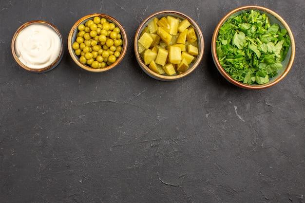 Bovenaanzicht van verschillende salade-ingrediënten van bonen en greens op donkere ondergrond