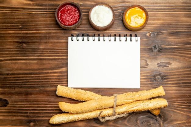 Bovenaanzicht van verschillende smaakmakers met broodjes en notitieblok op bruine tafel