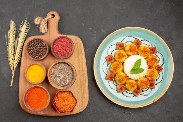 Bovenaanzicht van verschillende smaakmakers met gekookte rijst en gehaktballen op zwart
