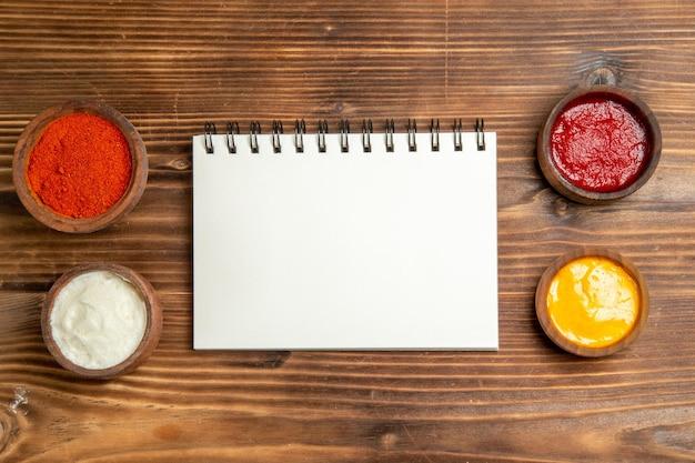 Bovenaanzicht van verschillende smaakmakers met notitieblok op bruin houten tafel pittige ketchup tomatenhout