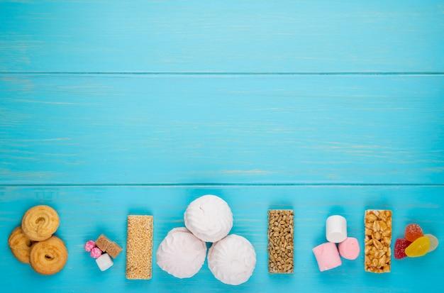 Bovenaanzicht van verschillende snoep honing staven van noten en zaden marshmallow en koekjes op blauw