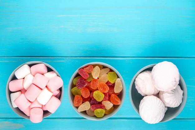 Bovenaanzicht van verschillende snoepjes kleurrijke marmelade snoepjes met witte zephyr en marshmallows in kommen op blauw