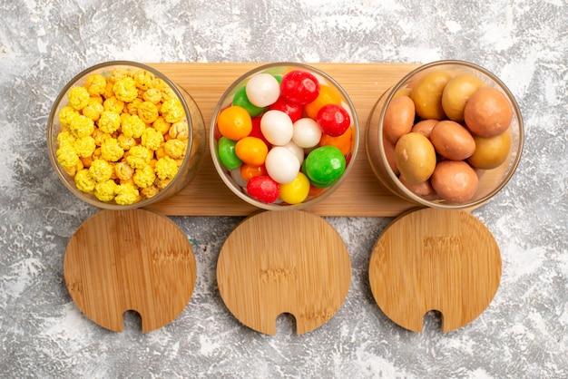Bovenaanzicht van verschillende snoepjes kleurrijke snoepjes op witte ondergrond